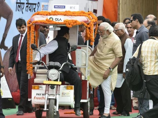 Prime Minister Narendra Modi inaugurates the first e-rickshaw booked through the Ola App as part of the 'Stand up India' initiative in Noida.