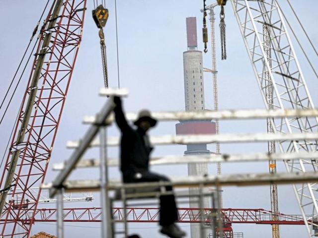 A worker looks on as the Lotus Tower construction site, backed by Chinese investment, is seen behind him in Colombo.