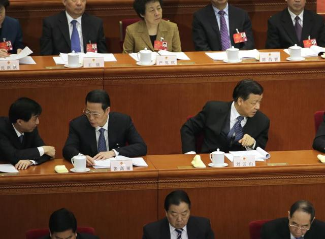 Chinese Communist Party Politburo Standing Committee members Liu Yunshan, second from right, and Zhang Gaoli, second from left, chat with other members during a plenary session of the National People's Congress at the Great Hall of the People in Beijing.