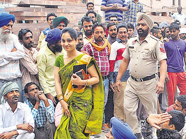 Municipal commissioner Sonali Giri walking past protesting workers on her joining day in Amritsar on Wednesday. She is the first woman MC commissioner of the city. Sameer Sehgal/HT
