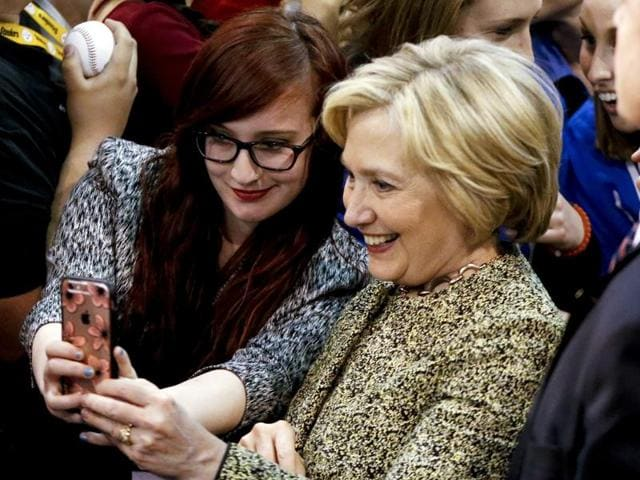 Democratic presidential candidate Hillary Clinton poses for a selfie with a supporter.  The former secretary of state is losing more of the white male vote to Bernie Sanders than when she ran against Barack Obama.