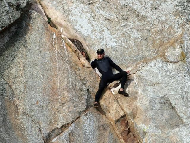 In this photo provided by Bob Isenberg, Michael Banks is stranded on a ledge some 80 feet off the ground on Morro Rock, e a landmark in Morro Bay.