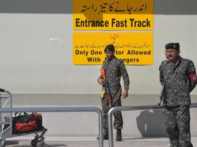A  gestures to security personnel as he arrives at a checkpoint at Benazir Bhutto International Airport in Islamabad. The US has warned its citizens against all non-essential travel to Pakistan.