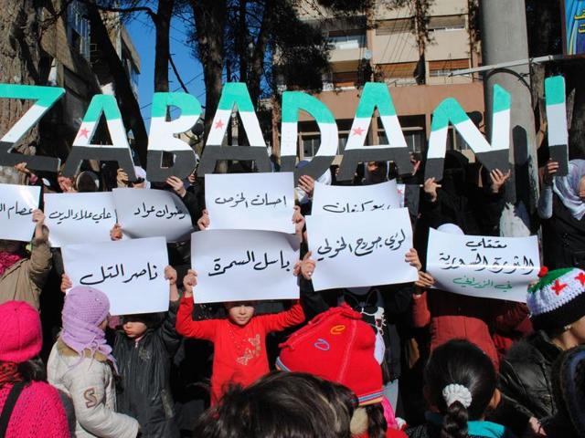 In this January 20, 2012, file photo, anti-Syrian regime protesters hold up placards with the names of opposition detainees during a demonstration at the mountain resort town of Zabadani, Syria, near the Lebanese border.