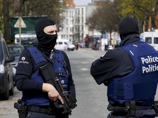 A police officer talks with a resident on the Avenue des Casernes in Etterbeek, Brussels, during a police action on April 9, 2016.