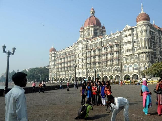 Tourists take photographs outside the iconic Taj Mahal Palace and Hotel in Mumbai.
