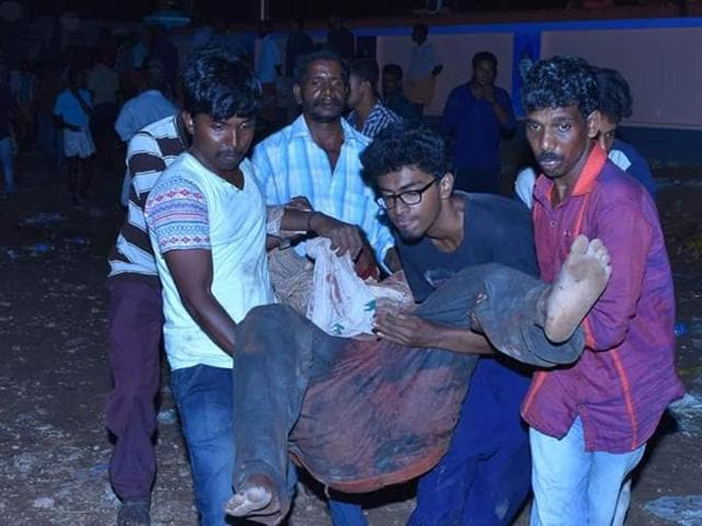 Visitors to the Puttingal temple in Paravur help carry out  those injured in the fire to safety.