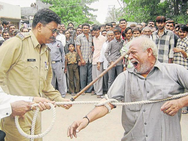 A police inspector publicly humiliates and beats a man accused of raping his daughter-in-law in Rajkot. The city police continue to indulge in the practice of public shaming called 'Sarbhara'.
