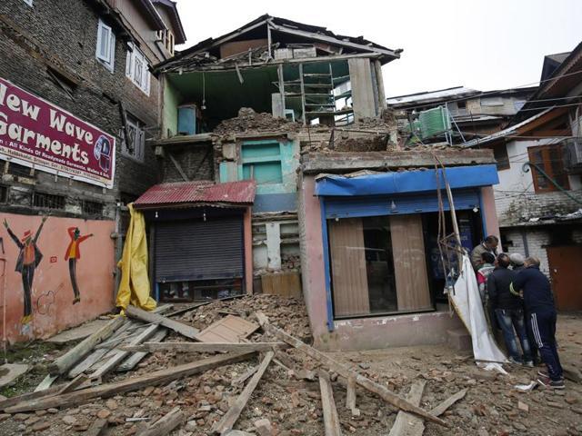Kashmiri men walk near a house damaged by an earthquake in Srinagar.
