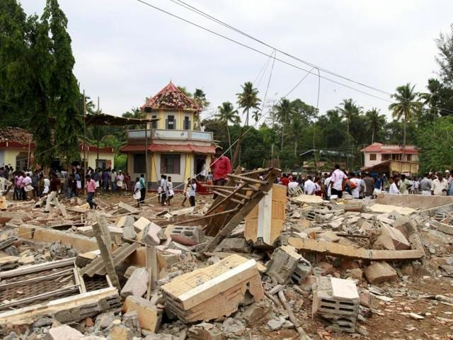 People walk past the debris of a godown that blew up after a fire engulfed it in Kollam, Kerala.