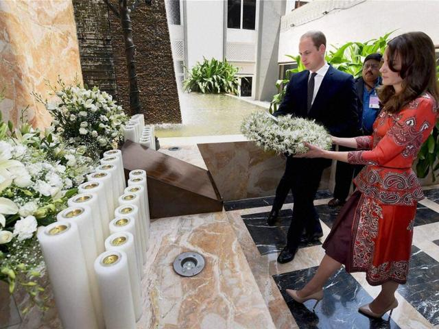 Britain's Prince William and his wife Catherine, Duchess of Cambridge, stand after paying their respects at the 26/11 memorial at the Taj Mahal Palace hotel.