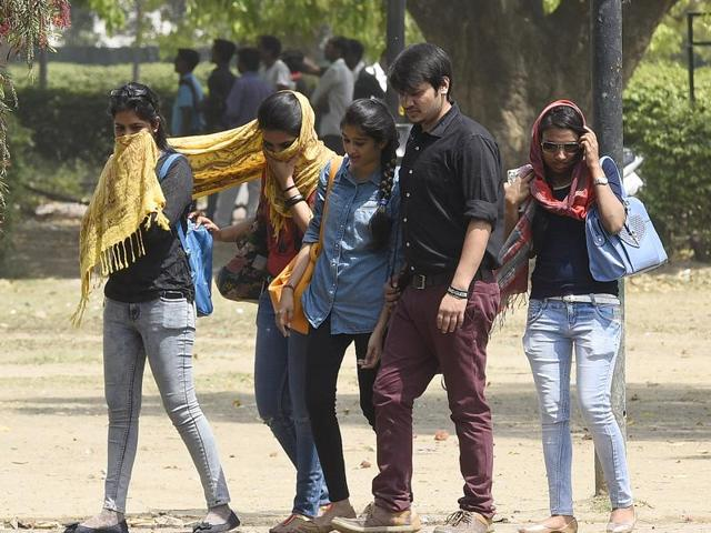 People cover themselves to protect themselves from the heat, in New Delhi.
