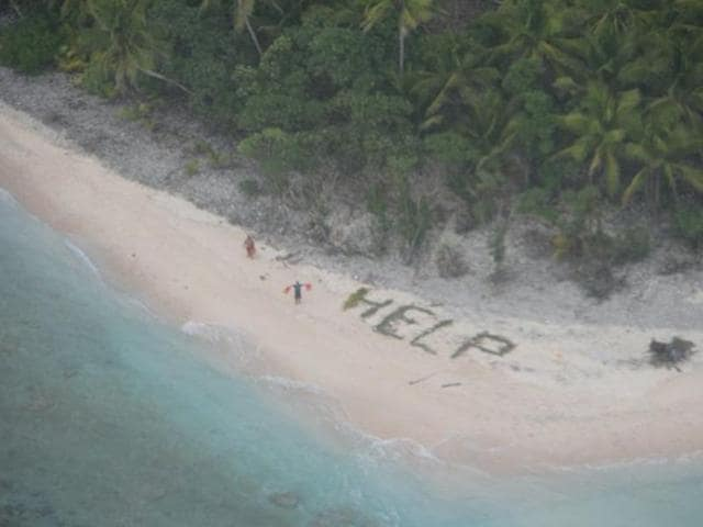 Three men rescused from island,Men write help on beach,US Navy