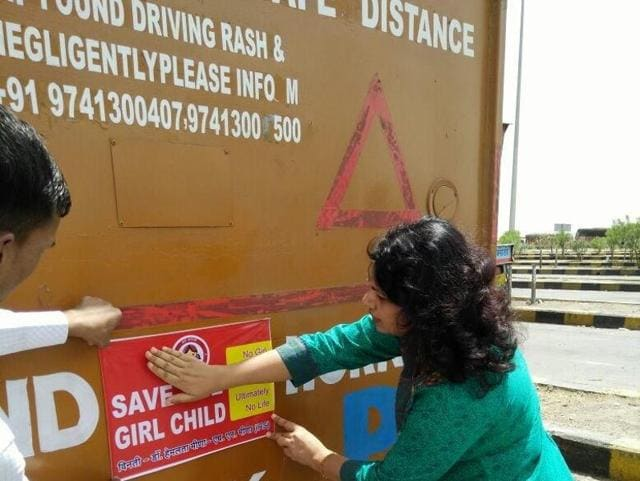 Prof Hemlata Meena pastes a sticker on 'save girl child' on a truck in Neemuch on Sunday.