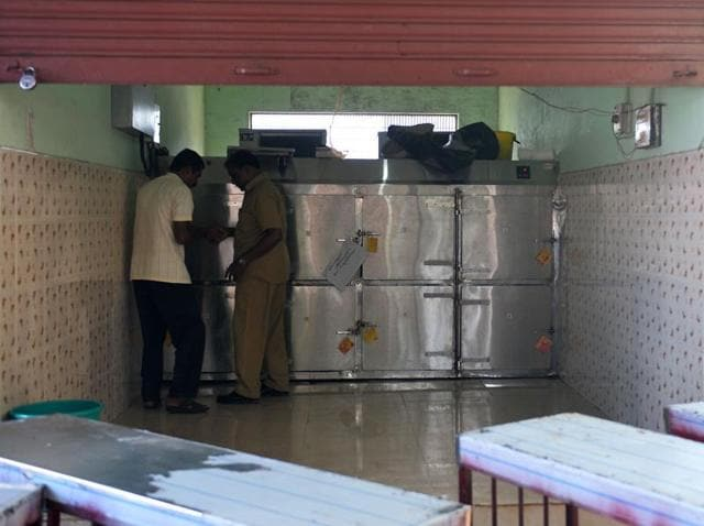 Hospital staff officials look at tags on freezers where unclaimed bodies have been kept at the mortuary of Kollam District Hospital, near Paravur.