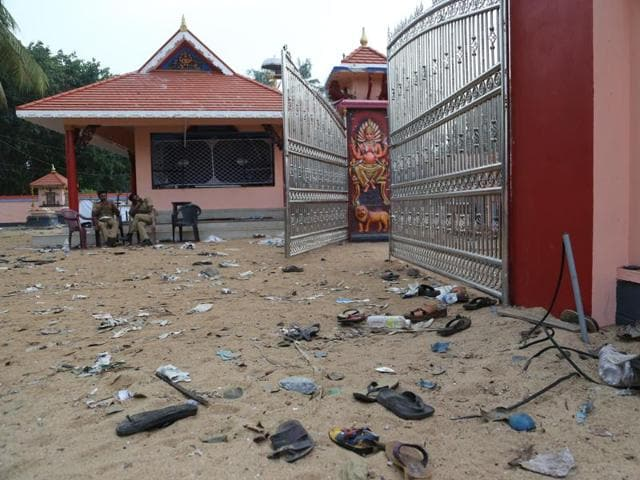 Footwear of the devotees lie scattered inside the temple compound where a fire broke out during a fireworks display at the Puttingal temple complex in Paravur village, Kollam district, Kerala.