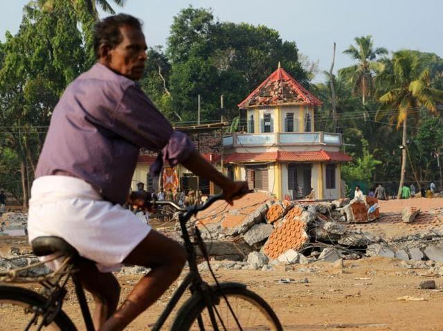 A cyclist rides past damaged structures at the spot where a massive fire broke out during a fireworks display at the Puttingal temple complex in Paravur village, Kollam district.