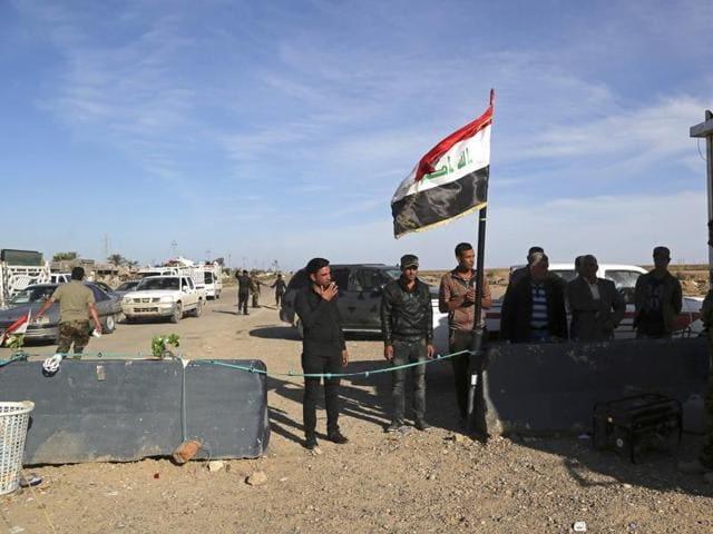 Civilians wait to be checked at a checkpoint at the entrance to Ramadi, 115 km west of Baghdad, Iraq, Sunday.