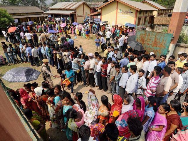 Voters wait in queues to cast votes at a polling station at Bonda during assembly elections in Kamrup district of Assam on Monday.