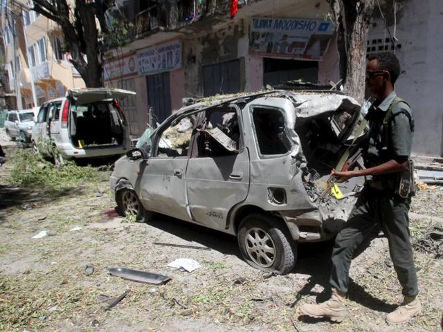 A Somali policeman walks to secure the wreckage of a car destroyed in a bomb explosion at a local government headquarters that killed five people in Somalia's capital Mogadishu.