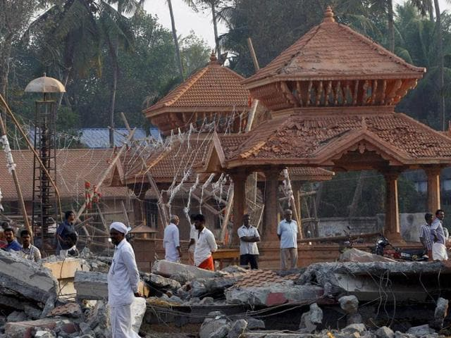 People check out the damaged structures after a massive fire broke out Sunday during a fireworks display at the Puttingal temple complex in Paravoor village.