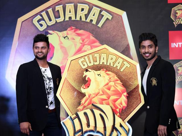Owner of Indian Premier League's Rajkot team and director of Intex Technologies, Keshav Bansal (R) along with cricketer Suresh Raina unveils the logo of the team at a press conference in New Delhi on February 2, 2016.