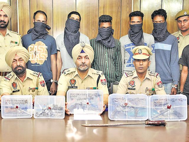 Police officials displaying the wepons seized from accused (in the background) at a press conference in Jalandhar on Monday.