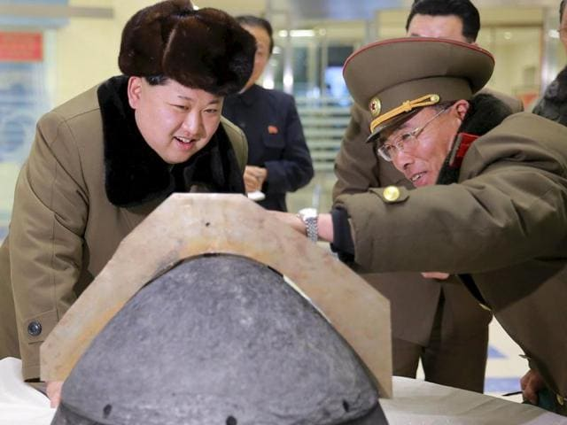 North Korean leader Kim Jong Un looks at a rocket warhead tip after a simulated test of atmospheric re-entry of a ballistic missile at an unidentified location in  North Korea.
