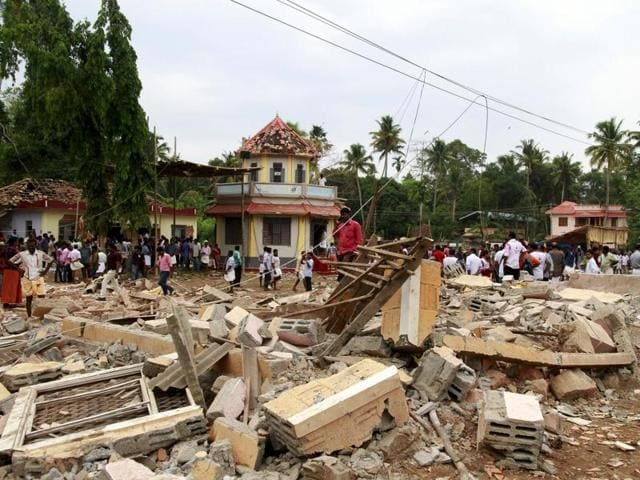 People walk past debris after a fire broke out at a temple in Kollam in the southern state of Kerala, India, April 10, 2016.