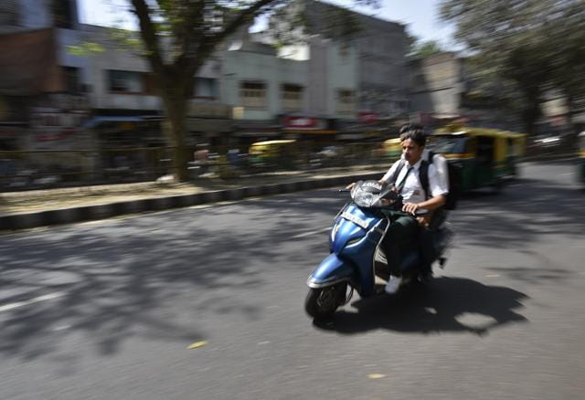 School children riding a scooter at Daryaganj in Delhi. In 2015, 225 fines were issued for underage driving.