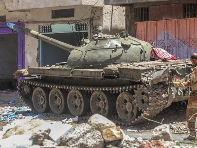A Yemeni fighter loyal to the country's exiled president walks past a tank on a road in the southwestern city of Taez on April 11, 2016.