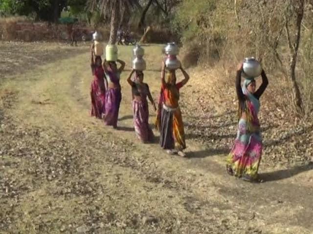 Women draw water from a well near Dewali village.