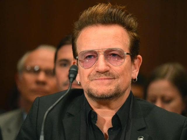 Bono, lead singer of rock band U2 and humanitarian activist (centre), poses with members of the activist group Code Pink as he arrives to testify at a Senate appropriations subcommittee in Washington on Tuesday.