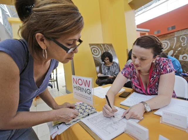 A'GACI clothing store hiring manager Marcie Lowe, right, gives her card to job applicant Xionara Garcia, left, of Miami, during a job fair at Dolphin Mall in Miami. Weekly applications for jobless benefits fell 13,000 to a seasonally adjusted 253,000, the Labor Department said