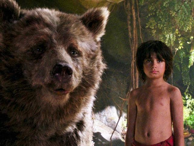 Mowgli, portrayed by Neel Sethi, right, and Baloo the bear, voiced by Bill Murray, appear in a scene from, The Jungle Book.