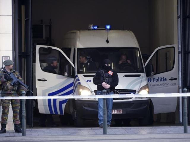 Police officers arrive aboard a vehicle at Brussels courthouse on April 13, 2016, before the hearing of top Paris attacks suspect Mohamed Abrini.