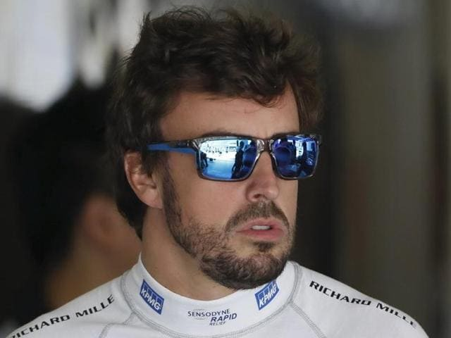 McLaren Formula One driver Fernando Alonso of Spain arrives at his garage during the first practice session.