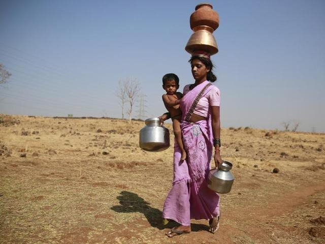 In this April 12, 2016 photo, a woman carries water from a spring at Raichi Wadi village, 120 kilometers (75 miles) north-east of Mumbai, India.(AP)