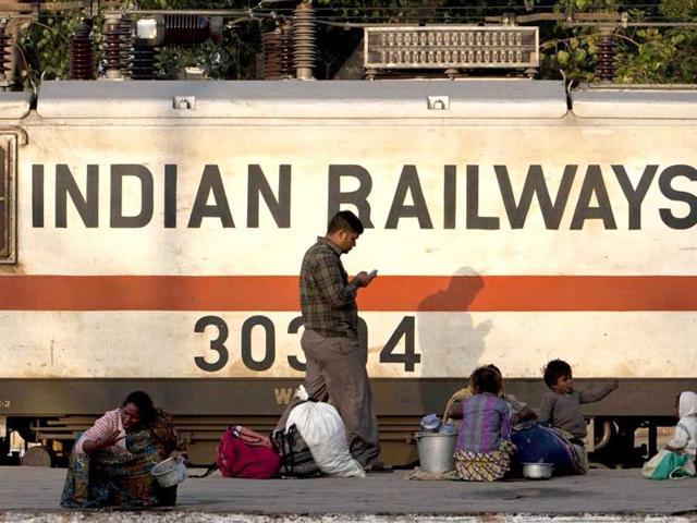 An Indian Railways worker cleans a coach.