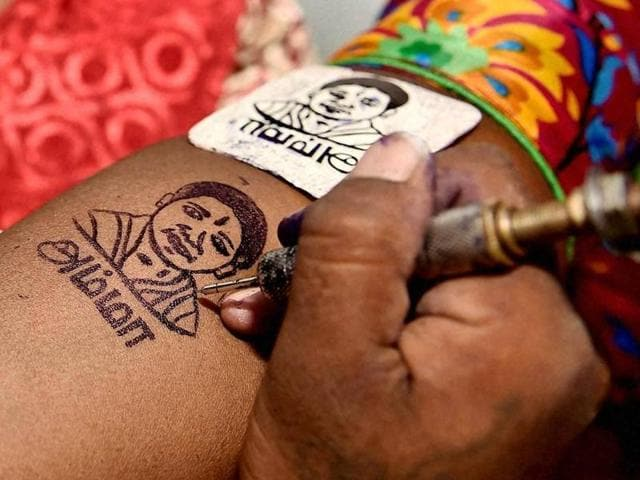 AIADMK cadres getting their hands tattooed with the image of Tamil Nadu chief minister J Jayalalithaa.
