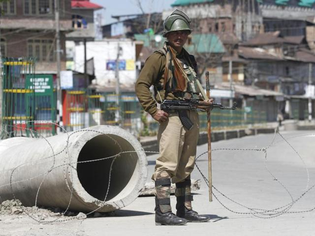 A boy is seen riding a bicycle during restrictions imposed by police in Mausuma area of Srinagar.