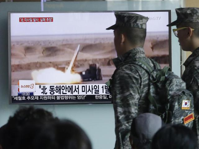 South Korean army soldiers pass by a TV news program showing a file footage of a missile launch conducted by North Korea at Seoul Railway Station.
