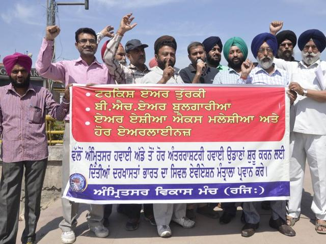 Members of different social organisations staging a protest against the Union civil aviation ministry for curtailing international flights from Guru Ram Das airport, in Amritsar on Friday.
