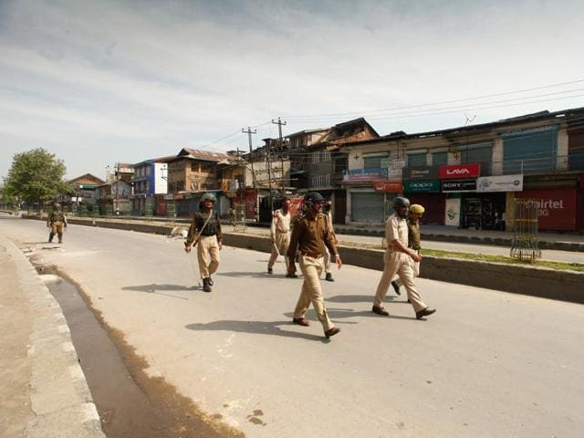 Securitymen  march on deserted road in downtown Srinagar  as tension grips Kashmir.