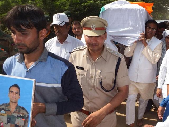 Haryana agriculture minister OP Dhankar among the pallbearers during the cremation of Major Amit Deswal at Surehti village in Jhajjar district on Friday.