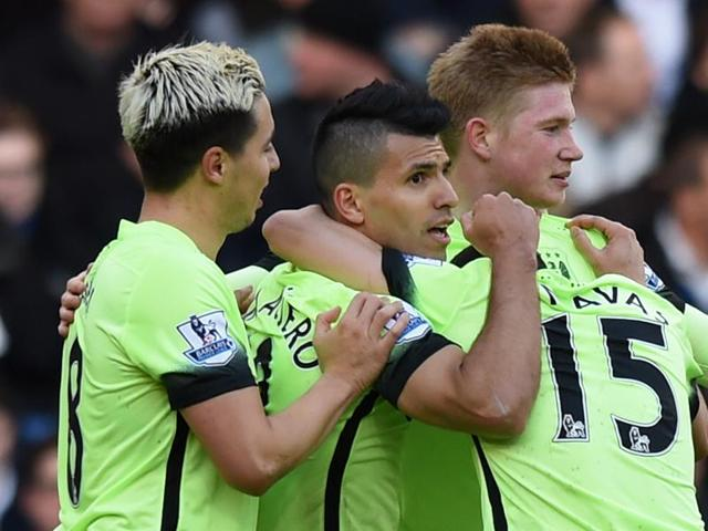 Sergio Aguero celebrates with teammates after scoring the first goal for Manchester City in the EPLgame against Chelsea at Stamford Bridge on April 16, 2016.