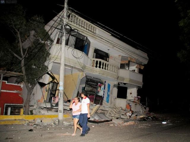 Residents walk on a street amid destroyed buildings following an earthquake in Guayaquil.