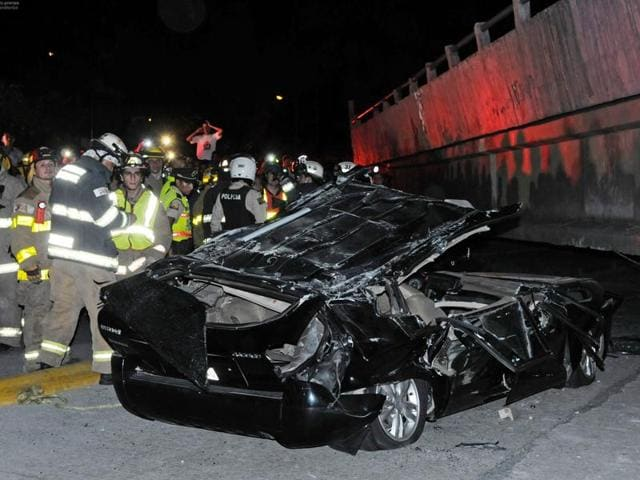 Rescue workers stand before a destroyed car after the collapse of a bridge in an earthquake.