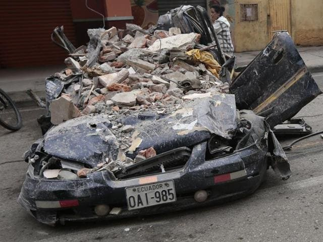 People walk past a car squashed by rubble after a 7.8-magnitude quake in Portoviejo, Ecuador.