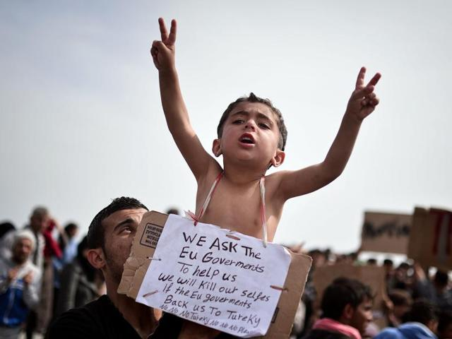 A Syrian refugee holds a child carrying a placard reading